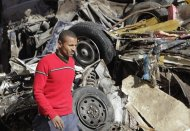 A man walks near a damaged vehicle after an explosion near a security building in Egypt's Nile Delta city of Mansoura in Dakahlyia province, about 120 km (75 miles) northeast of Cairo December 24, 2013. A car bomb tore through a police compound in Egypt's Nile Delta on Tuesday, killing 13 people and wounding more than 130, security officials said, in one of the deadliest attacks since the army deposed Islamist President Mohamed Mursi in July. REUTERS/Mohamed Abd El Ghany (EGYPT - Tags: POLITICS CIVIL UNREST)