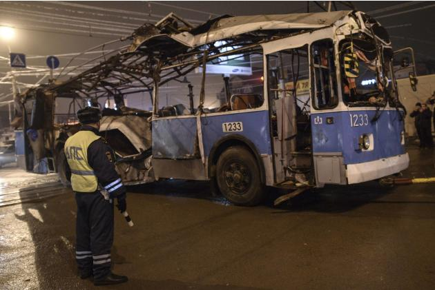 A policeman watches as a bus destroyed in an earlier explosion is towed away in Volgograd