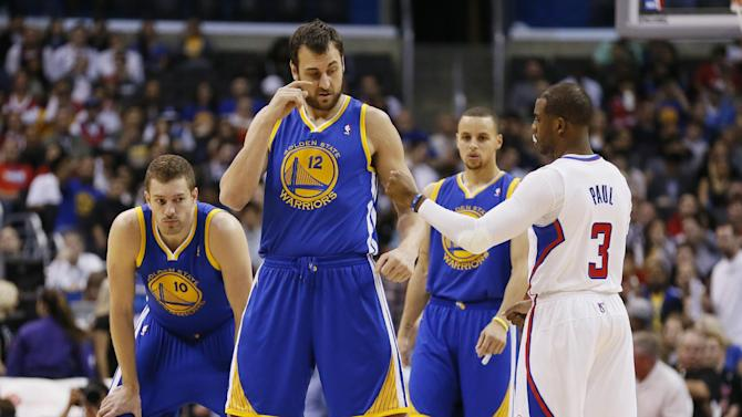 Golden State Warriors' Andrew Bogut, left, returns a fist-bump gesture from Los Angeles Clippers' Chris Paul, right, as Warriors' David Lee, rear left, and Stephen Curry, rear center, watch before an NBA basketball game in Los Angeles, Wednesday, March 12, 2014