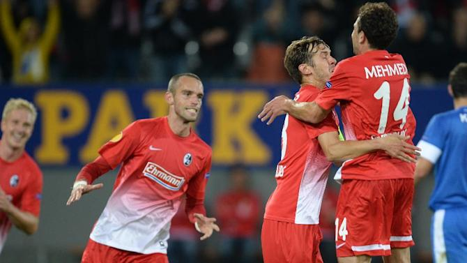 Freiburg's Julian Schuster  third from right,  celebrates with teammates  from left,  Mike Hanke  PavelKrmas and Admir Mehmedi after scoring the opening goal   during the UEFA Europa League Group H soccer match between SC Freiburg and Slovan Liberec FC  in Freiburg, Germany, Thursday Sept. 19,  2013