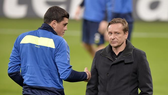 Schalke's Kyriakos Papadopoulos of Greece, left, talks to sporting manager Horst Heldt during a training session prior the Champions League Group E soccer match between FC Schalke 04 and FC Chelsea in Gelsenkirchen, Germany, Monday, Oct. 21, 2013