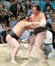"""Mongolian-born champion, or """"ozeki"""", Harumafuji (left) pushes his compatriot and grand champion, or """"yokozuna"""", Hakuho (right), out of the ring to take the title at the Nagoya Grand Sumo tournament in July. 2012"""