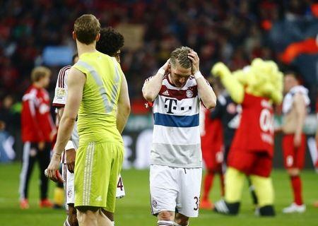 Bayern Munich's Schweinsteiger reacts next to team mates Neuer and Dante after their German first division Bundesliga soccer match against Bayer Leverkusen in Leverkusen