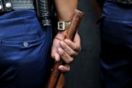 This file illustration photo shows a Philippine policeman holding his truncheon during a patrol in Manila, on March 20, 2012. A gunman shot dead three people and wounded several others when he opened fire in a crowded Philippine market on Friday, before he himself was shot dead, according to police