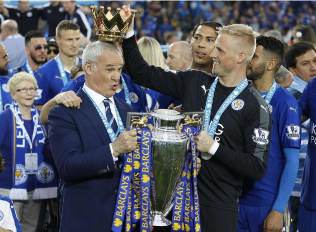 FILE - In this Saturday, May 7, 2016 file photo Leicester City team manager Claudio Ranieri has the crown of the trophy placed on his head by Leicester goalkeeper Kasper Schmeichel as they celebrate b