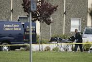 A police officer carries the body of a victim killed in a shooting rampage at a private religious college in Oakland, California on March 2. A Korean-American former student at a California religious college lined up his victims and shot them them execution-style, police said Tuesday