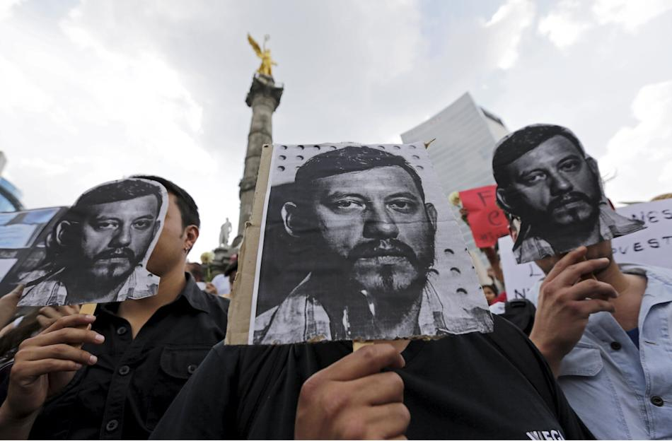 Journalists, photographers and activists hold up pictures of photojournalist Espinosa during a protest against his murder at the Angel of Independence monument in Mexico City