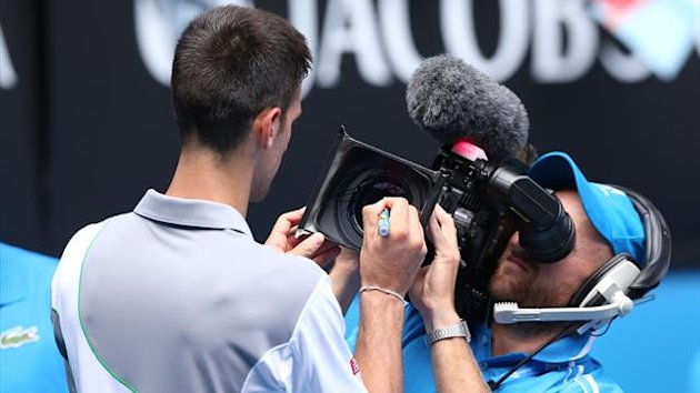 Novak Djokovic of Serbia signs his autograph on a camera lens after winning his second round match against Leonardo Mayer (Getty Images)