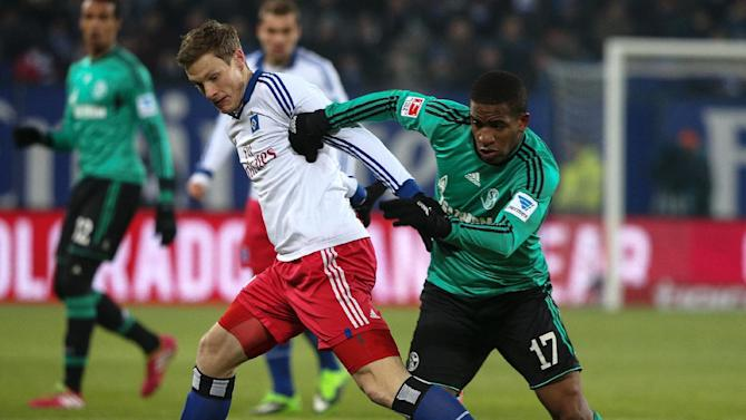 Hamburg's Marcell Jansen, left,  and Schalke's Jefferson Farfan  challenge for the ball during the Bundesliag soccer match between Hamburger SV and Schalke 04 in the Imtech-Arena in Hamburg, Germany,Sunday Jan. 26, 2014