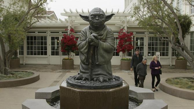 People walk past a fountain showing the Yoda character from the Star Wars movies outside of Lucasfilms headquarters in San Francisco, Tuesday, Oct. 30, 2012. The Walt Disney Co. announced Tuesday that it was buying Lucasfilm Ltd. for $4.05 billion. (AP Photo/Jeff Chiu)