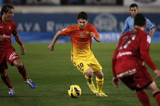 FC Barcelona's Lionel Messi from Argentina drives the ball next to RCD Mallorca's Joaqun Navarro Ximo, right, and Toms Pina, left, during a Spanish La Liga soccer match in Mallorca, Spain, Sunday, Nov. 11, 2012. (AP Photo/Tolo Ramon)