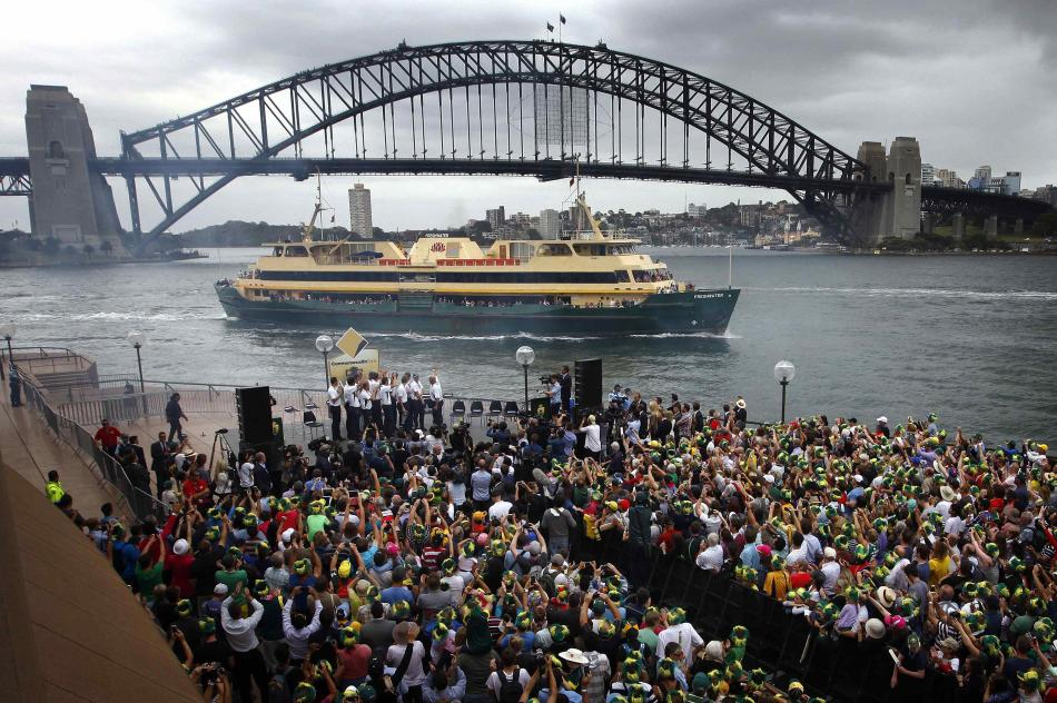 Members of the Australian cricket team wave to passengers sailing past on ferries during a public celebration ceremony at the Sydney Opera House