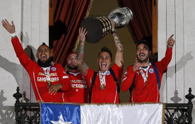 Santiago de Chile: Chilean soccer players Arturo Vidal (L), Eduardo Vargas (2-R) and Mauricio Pinilla (R) celebrate with the Copa America 2015 champions trophy from a balcony of La Moneda palace in Sa