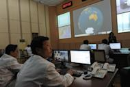 North Korean technicians work at the control room of the Tongchang-ri space center on April 8, 2012. The North insists its satellite launch was not banned under UN resolutions and did not breach a deal with the United States announced in February