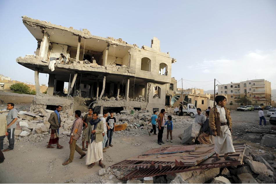 People stand at the site of an air strike in Sanaa