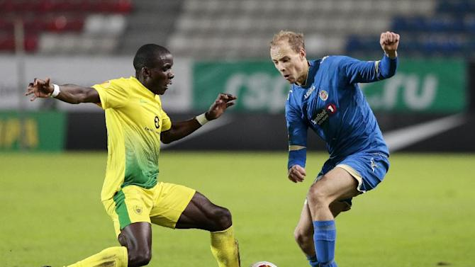 Anzhi's Benoit Angbwa, left, and Tromso's Ruben Kristiansen vie for the ball during the Europa League group K soccer match between Anzhi Makhachkala and Tromso IL at Saturn stadium in Ramenskoye, outside Moscow, in Russia, on Thursday, Oct. 24, 2013