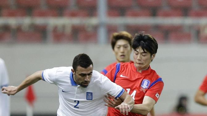 Greece's Giannis Maniatis, left, and South Korea's Ki Sungyueng fight for the ball during a friendly match at Georgios Karaiskakis stadium in Piraeus port, near Athens, Wednesday, March 5, 2014