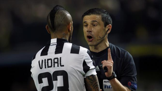 Vidal of Juventus argues with referee Mazic of Serbia during the Champions League round of 16 second leg soccer match against Borussia Dortmund in Dortmund