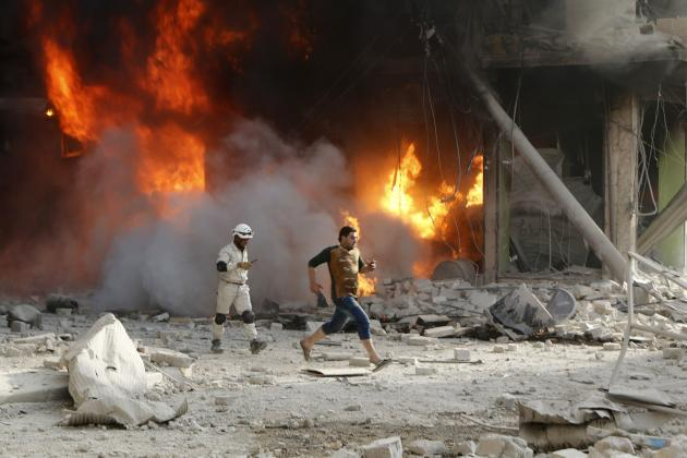 Member of the Civil Defence and a resident pass a fire at a site hit by what activists said were barrel bombs dropped by forces loyal to Syria's President Assad in Aleppo