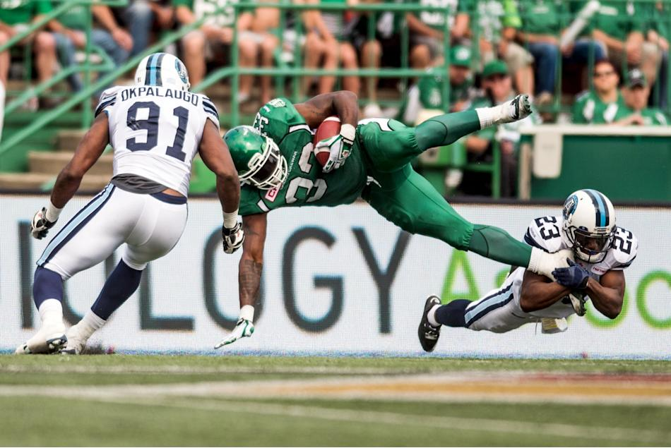 Saskatchewan Roughriders running back Messam is tackled by Toronto Argonauts defensive back Agnew and Toronto Argonauts defensive lineman Okpalaugo during the second half of their CFL football game in