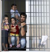 Syrians are seen behind a fence at a detention centre in the city of Lubimets, some 30 km (19 miles) northwest from Kapitan Andreevo-Kapikule border checkpoint with Turkey, August 28, 2013. As Washington weighs a military strike against Syrian leader Bashar al-Assad, the human fallout of two and a half years of conflict that has sent millions to flight is no longer contained to the Middle East. Due to lack of capacity at Bulgaria's three refugee centres, many Syrians are sent to stricter detention centres which they are not allowed to leave, kept for months behind walls topped with razor-wire and windows with bars. Picture taken August 28, 2013. To match Feature SYRIA-CRISIS/BALKANS REUTERS/Stoyan Nenov (BULGARIA - Tags: POLITICS CONFLICT SOCIETY IMMIGRATION)