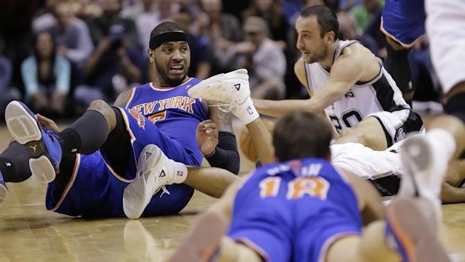 New York Knicks' Carmelo Anthony, left, and Beno Udrih (18) and San Antonio Spurs' Manu Ginobili (20), of Argentina, hit the floor as they chase a loose ball during the second half on an NBA basketball game, Thursday, Jan. 2, 2014, in San Antonio.  New York won 105-101
