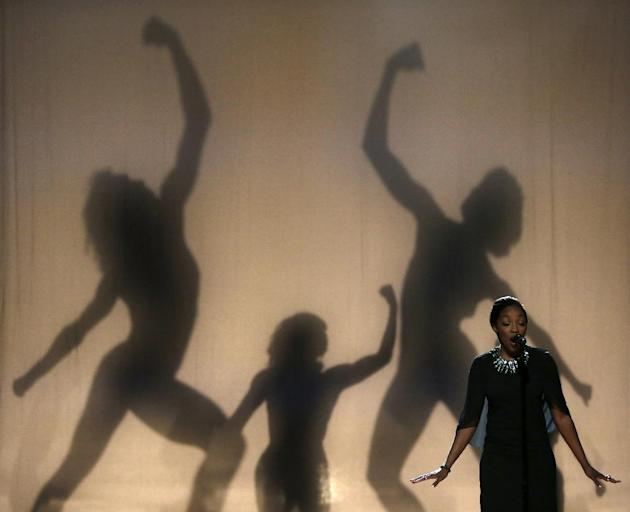 Musician Estelle, right, performs as dancers are silhouetted behind her during a taping of the Black Girls Rock award ceremony at the New Jersey Performing Arts Center, Saturday, March 28, 2015, in Ne