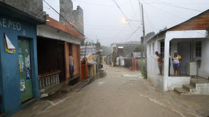 Residents watch from their homes as floodwaters run down a street in the Cristo Redentor, or Christ Redeemer neighborhood in Santo Domingo, Dominican Republic, Wednesday, July 10, 2013. Tropical Storm Chantal was downgraded Wednesday to a tropical wave as its scattered clouds drifted quickly westward toward Jamaica. But heavy rains from the weakened system continued to drench parts of Haiti and the Dominican Republic and force the evacuation of thousands from flood-prone areas. (AP Photo)