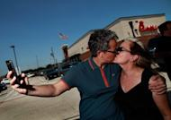 "A couple kiss outside a Chick-fil-A restaurant on August 3, in Dallas, Texas. Gays and lesbians puckered up at ""kiss-ins"" outside Chick-fil-A outlets across the United States in protest over the fast-food chain's opposition to same-sex marriage"