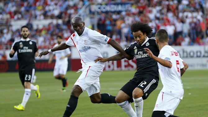 Real Madrid's Marcelo is challenged by Sevilla's Stephane Mbia and Diogo Gomes Figueiras during their soccer match in Seville