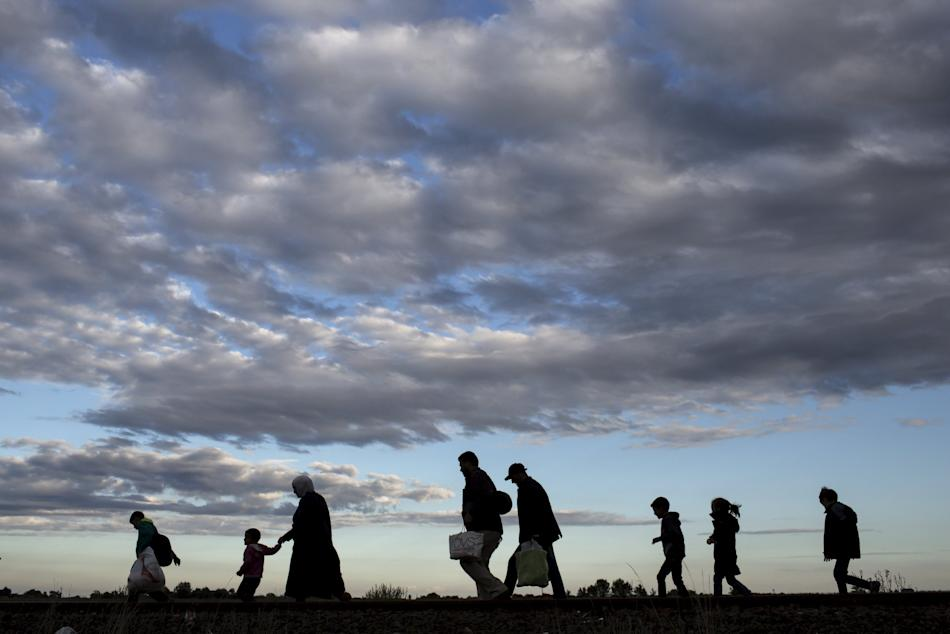 Migrants walk along rail tracks as they arrive to a collection point in the village of Roszke, Hungary