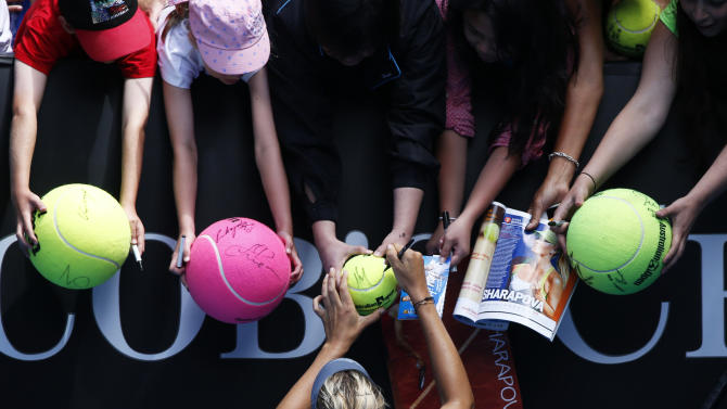 Maria Sharapova of Russia signs autographs after defeating compatriot Olga Puchkova in their women's singles match at the Australian Open tennis tournament in Melbourne