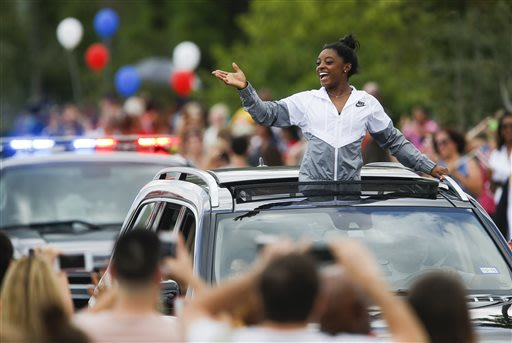 Simone Biles acknowledges the crowd during a welcome home parade in Texas. (AP)