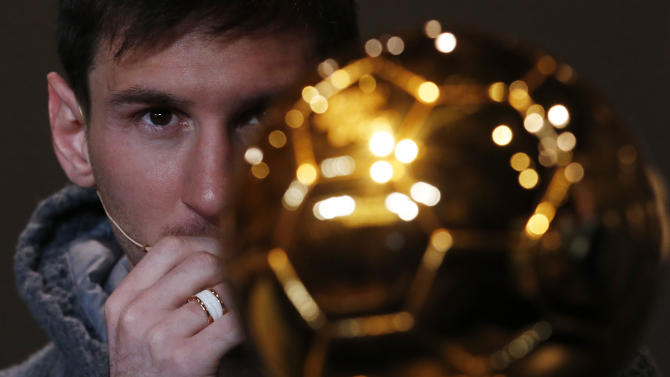 FIFA Men's Ballon d'Or of the Year 2012 nominee Messi of Argentina looks at the trophy during a news conference before the FIFA Ballon d'Or 2012 soccer awards ceremony at the Kongresshaus in Zurich