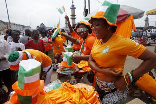 Fans buy national team merchandise ahead of the Ivory Coast's African Nations Cup final against Ghana, in Abidjan