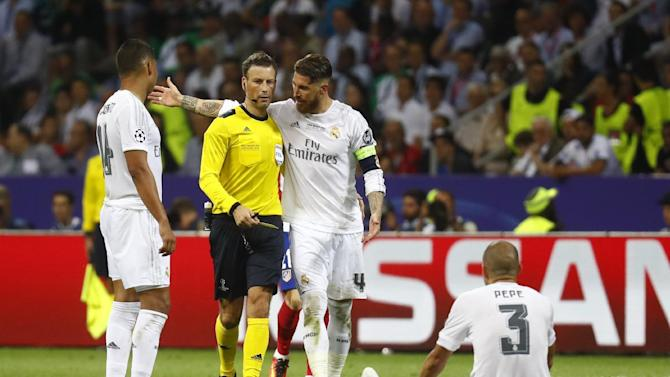 Real Madrid's Pepe is on the floor after fouling Atletico Madrid's Gabi and is shown a yellow card by referee Mark Clattenburg