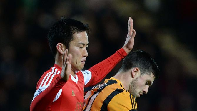 Southampton's Maya Yoshida challenges Hull City's Long during their English Premier League soccer match at the KC Stadium in Hull