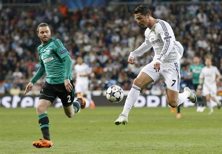 Real Madrid's Cristiano Ronaldo (R) controls the ball next to Schalke 04's Tim Hoogland during their Champions League last 16 second leg soccer match at Santiago Bernabeu stadium in Madrid March 18, 2014. REUTERS/Paul Hanna