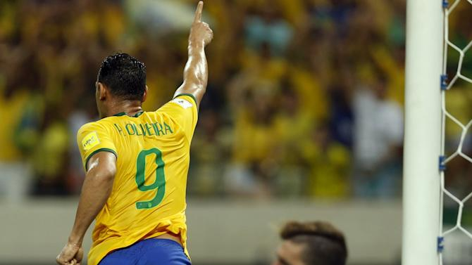 Oliveira of Brazil celebrates his goal as goalkeeper Alain Baroja of Venezuela reacts during their 2018 World Cup qualifying soccer match in Fortaleza, Brazil