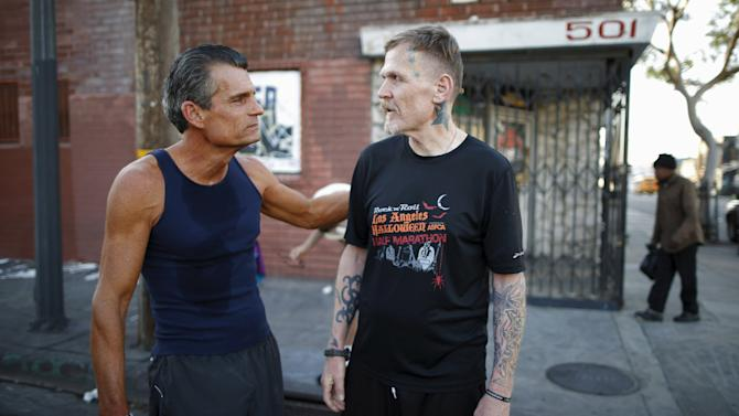 Los Angeles Superior Court Judge Craig Mitchell, 58, congratulates Ben Shirley, 50, after a Midnight Mission Running Club sunrise run through Skid Row in Los Angeles