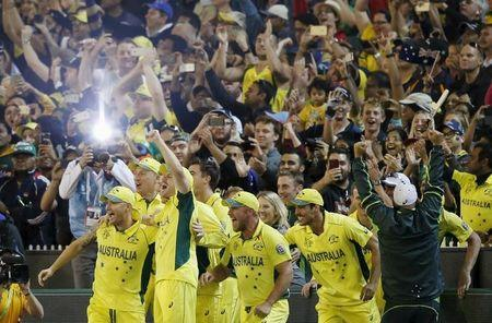 Members of the Australian cricket team run onto the field after Steven Smith hit the winning runs to defeat New Zealand in their Cricket World Cup final match at the Melbourne Cricket Ground