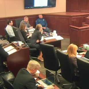 FILE - In this image taken from Colorado Judicial Department video, Colorado theater shooter James Holmes, left rear in light-colored shirt, watches during testimony by witness Derick Spruel, upper right, on the second day of his trial in Centennial, Colo., Monday, April 27, 2015. Standing at left is prosecutor Lisa Teesch-Maguire. Defense attorneys have urged jurors not to let emotions sway them, but with weeks of harrowing testimony still to come, experts say James Holmes' lawyers will have a difficult time convincing jurors to put sympathy behind them as they decide whether he was legally insane when he killed 12 people and injured 70 others in July 2012. (Colorado Judicial Department via AP, Pool, File)