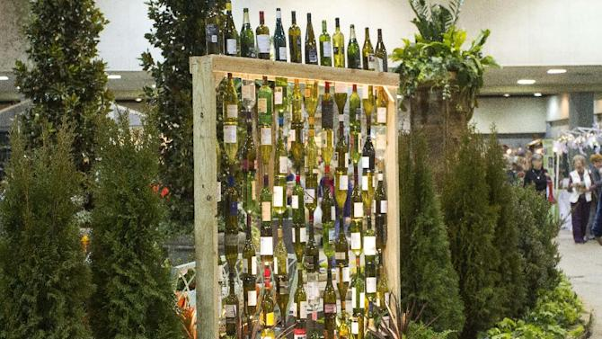 "In this publicity photo provided by Chris H. Olsen, the Landscape Designer, Olsen, of Little Rock, Ark., created a decorative wall out of empty wine bottles by threading them onto metal poles inserted into a wooden frame. Olsen shares outdoor decorating ideas in his book ""Chris H. Olsen's Five Seasons"" (Leisure Arts, 2011). (AP Photo/Chris H. Olsen, Janet Warlick/Camera Work)"