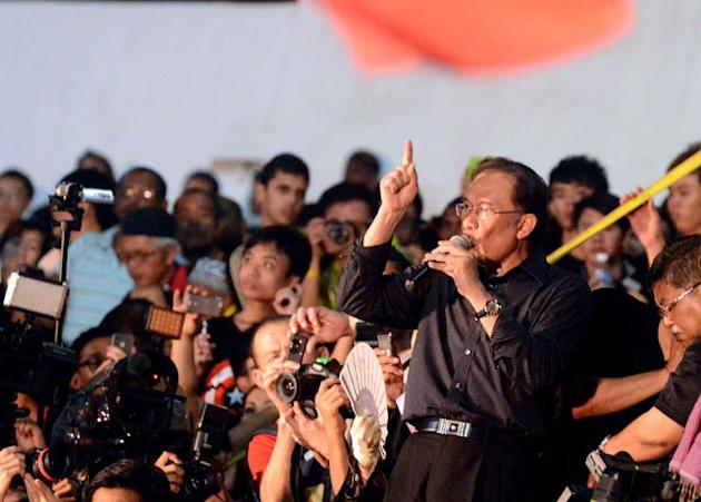 """Malaysian opposition leader Anwar Ibrahim (R) speaks during a rally at a stadium in Kelana Jaya, Selangor on May 8, 2013. Anwar called Malaysia's recent elections """"the mother of all frauds"""" as he kept up the pressure over polls he says were stolen by the 56-year-old regime"""
