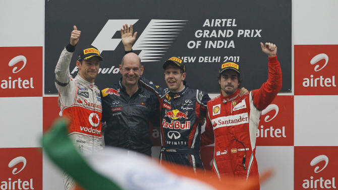 Winner Red Bull driver Sebastian Vettel of Germany, second from right, poses with Ferrari driver Fernando Alonso of Spain, right, third place, Red Bul chief technical officer Adrian Newey and McLaren Mercedes driver Jenson Button of Britain, second place, celebrate on the podium after the Indian Formula One Grand Prix at the Buddh International Circuit in Noida, 38 kilometers (24 miles) from New Delhi, India, Sunday, Oct. 30, 2011. (AP Photo/Gurinder Osan)