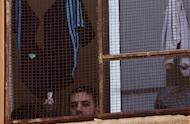 A Syrian rebel fighter who surrendered to the government during the siege of Homs stands behind a window at the Al-Andalous school turned into a detention center on May 13, 2014