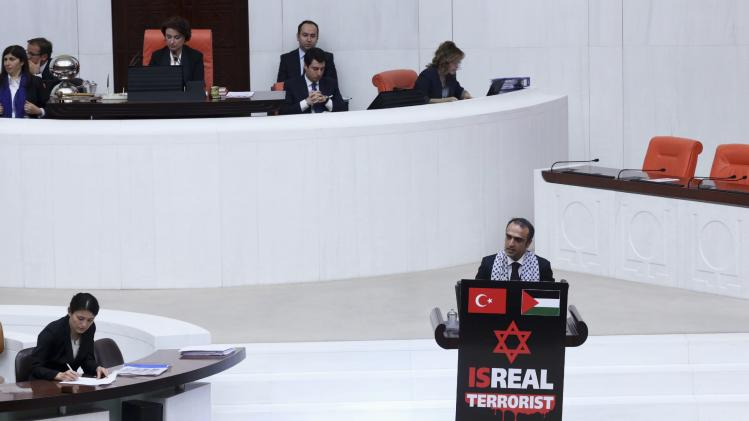 Turkey's ruling AK Party MP Cuma Icten speaks against Israel's military action in Gaza after hanging banner to rostrum during debate at Turkish Parliament in Ankara
