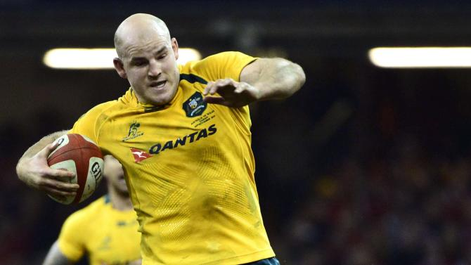 Australia's Moore evades the tackle of Wales's Jenkins during their international rugby union match in Cardiff