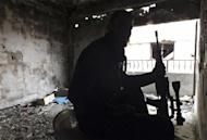 A Free Syrian Fighter holds his weapon inside a damaged building in the besieged area of Homs, January 4, 2014. REUTERS/Yazan Homsy