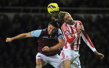 West Ham United's Carroll and Stoke City's Crouch challenge for an aerial ball during their English Premier League soccer match in London
